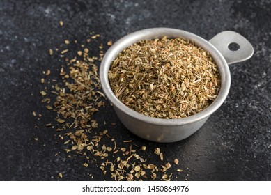 Dried Oregano Spilled from a Measuring Cup