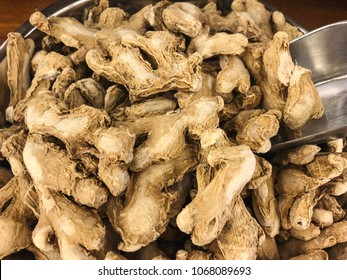 Dried organic ginger with metallic scoop close up.