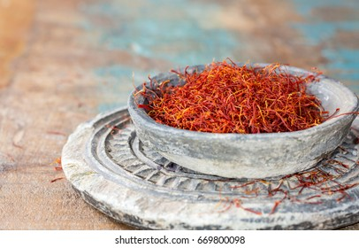 Dried organic red saffron Spice on wooden background close up copy space