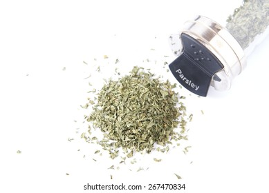 Dried parsley flakes piled on a white background with spice jar lying on its side.