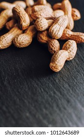 Dried peanuts with the shell on black background, selective focus, close up, copy space