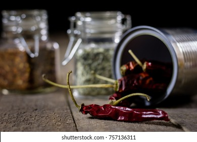 Dried pepper in a metal tin on a wooden kitchen table. Red hot pepper and spices in the kitchen. black background