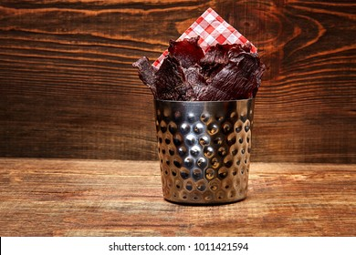 Dried peppered beef jerky cut in strips in a metal bucket on wooden background. Serving the dish in a restaurant
