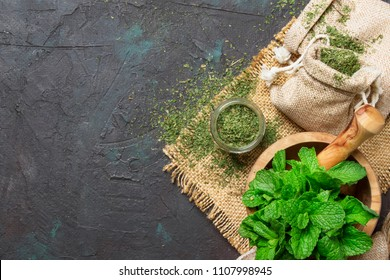 Dried peppermint in a glass jar and a bunch of fresh mint, medicine herb on black background, top view