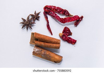 Dried peppers, cinnamon stick and anise star isolated on white background closeup