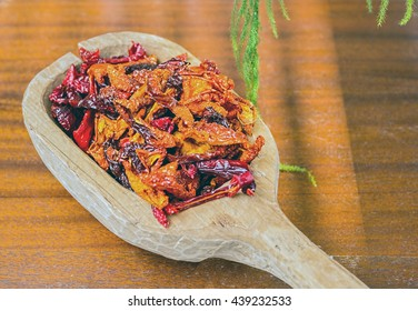 Dried peppers in a large wooden spoon.