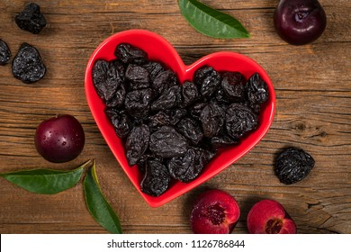 Dried Plums Pitted Prunes in Heart Shaped Bowl Background. Selective focus.