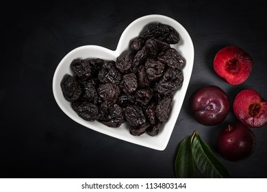 Dried Plums Pitted Prunes in Heart Shaped Bowl on a black background. Selective focus.