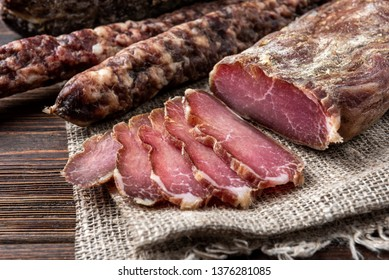 Dried pork meat and sausage on dark wooden background.