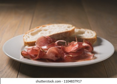 dried prosciutto ham on white plate