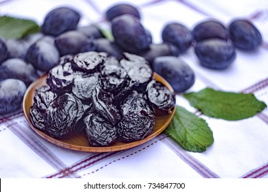 Dried prunes in a dish on a tablecloth on the background of fresh plums. Prunes and plums on the kitchen table closeup.