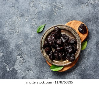 Dried prunes on plate. Top view of peeled plums. Top view.