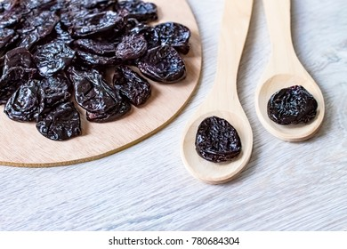 Dried prunes on the table and in wooden spoons closeup. Fresh sweet prunes closeup.