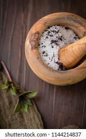 Dried Purple Basil Herb in Wooden Mortar and Pestle to make Herb Salt; Fresh Sprig of Herb on Wooden Tabletop