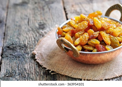 Dried raisins in a copper bowl on the old wooden background