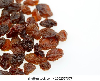Dried raisins stacked on a white background