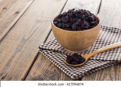 Dried raisins in wooden cup and spoon on wooden table.