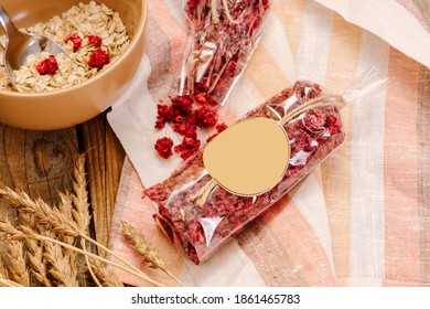 Dried raspberries in plastic packaging on wooden background. Space for text