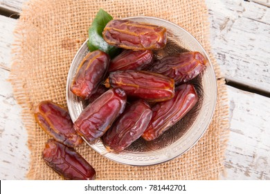 Dried Raw Organic Medjool date fruit and green mint in a silver metal bowl on old white wooden table close up. The Date Palm fruit is known as a date. Only female trees produce dates.