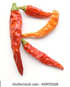 Dried red cayenne chili peppers organized in the shape of the letter R - isolated