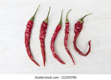 Dried red chili's on a wooden chopping board.