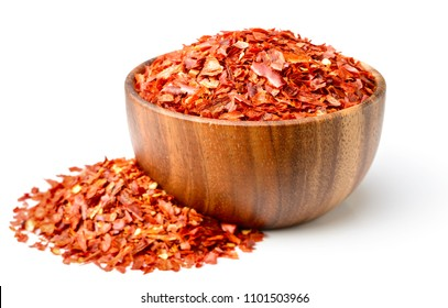 dried red chilli flakes in the wooden bowl, isolated on white background