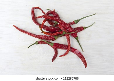 Dried red chilli's on a wooden chopping board.