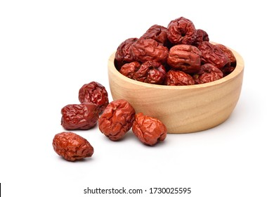 Dried red date or Chinese jujube fruits in wooden bowl isolated on white background.