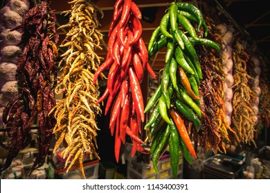 Dried red and green chili peppers hanging in Barcelona Market (Mercat de Sant Josep de la Boqueria) on the La Rambla street, Barcelona, Spain