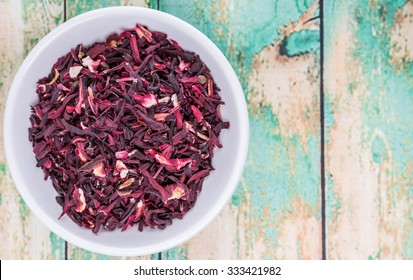 Dried red hibiscus tea leaves in white bowl over wooden background