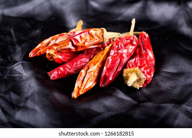 Dried red hot peppers over black silky background, horizontal image