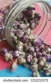 Dried rose buds. Rosebud tea drink in a glass jar on pink and blue background