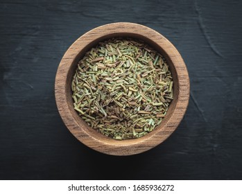 Dried rosemary in wooden bowl on dark vintage background. Overhead shot.