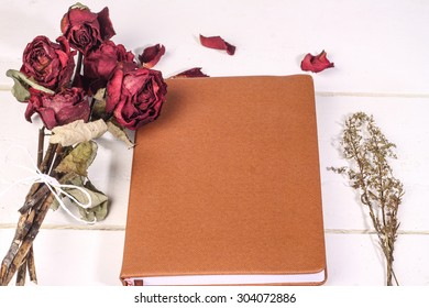 dried roses isolated with book on white wooden background