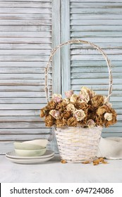 Dried roses in white wicker basket and crockery against wooden blinds. Shabby chic interior decor.