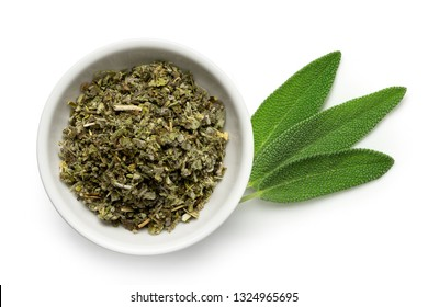 Dried rubbed sage in a white ceramic bowl next to fresh sage leaves isolated on white from above.