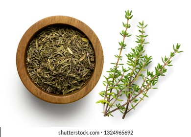 Dried rubbed thyme in a dark wood bowl next to fresh thyme sprig isolated on white from above.