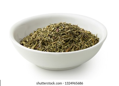 Dried rubbed thyme in a white ceramic bowl isolated on white.