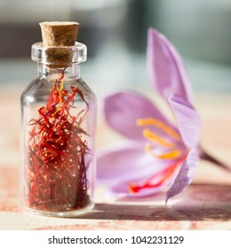 Dried saffron spice in a bottle and Saffron flower