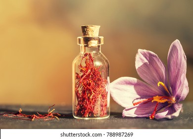 Dried saffron spice  in a bottle and Saffron flower