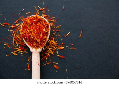 Dried saffron spice on black background. Raw Organic pistil powder saffron are scattered on the table.
