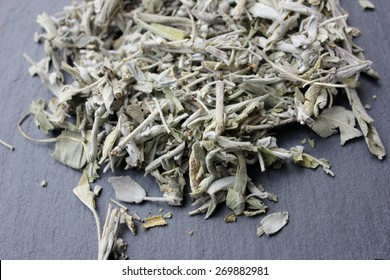 Dried sage plant (salvia officinalis) leaves (whole herb) for incense or herbal tea infusion on a grey slate stone background, natural feeling used by the ancient native indians for rituals