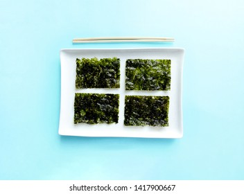Dried seaweed and chopsticks. Nori chips on a white ceramic plate, seaweed sheets, macro, close-up.Healthy food concept.top view, flat lay.