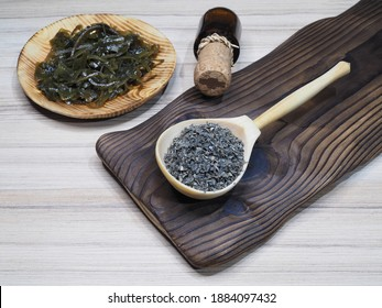 Dried seaweed laminaria in a wooden spoon, drinking kelp extract in a bottle and salad in a plate on a wooden kitchen board, flat layout. Useful kale with iodine for use in food and cosmetology
