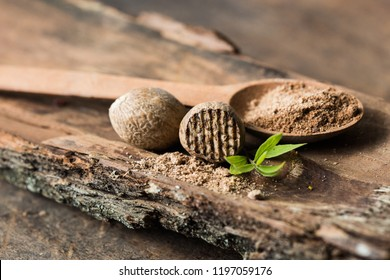 Dried seeds of fragrant nutmeg on wooden  background.