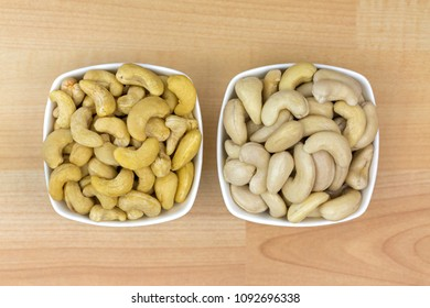 Dried and soaked Cashew nut seeds in white bowl on wooden background, top view