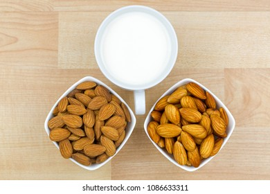 Dried and soaked Shelled Almond with cup of Almond Milk on wooden background, top view
