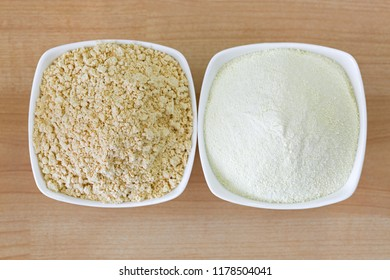 Dried soya powder next to milk powder, roasted ground soy bean flour powder compare to powdery animal cow milk in white bowl, top view on wooden background