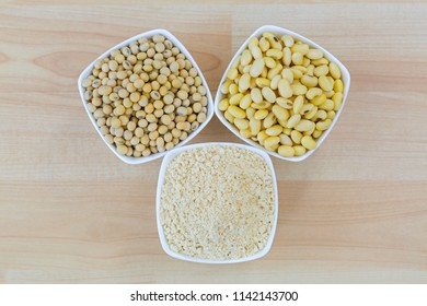 Dried soya, soaked soybean and roasted ground soy bean flour powder in white bowl, top view on wooden background