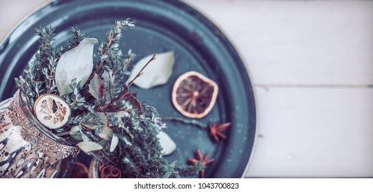 Dried spices on a plate on a white wooden background